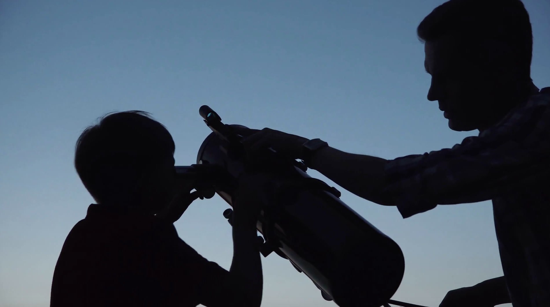Two people looking through telescope